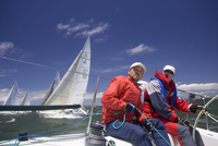 Crew On Stern Of Sailboat Racing In Regatta