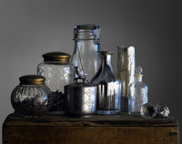 An Assortment Of Glass And Silver Jars On A Chest.