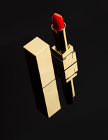 Red Lipstick In A Gold Case On A Black Background.