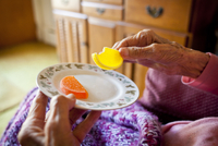 A Hands Only Photograph Showing Nonagenarian Eating Two Piec