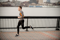 Man Running Along Walkway With Manhattan In Background Acros