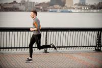 Man Running Along Walkway With Manhattan In Background Acros 20055011161| 写真素材・ストックフォト・画像・イラスト素材|アマナイメージズ