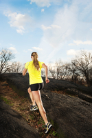 Woman Trail Running On A Rocky Trail In The Woods.