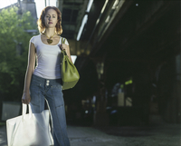 A Shopper Stands Next To The Train Tracks While Holding Her