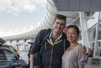 Two Friends Pose For A Photograph Together At The Airport.