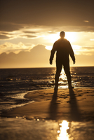 A Man Is Silhouetted By The Setting Sun At The Beach.