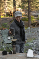 A Woman Enjoys Her Morning Cup Of Coffee At A Camp Site.