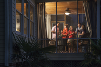 A Group Of People Talk On The Sun Porch At A Summer Party.