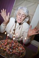 Senior woman wearing earphones around her neck with her birt