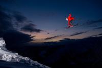 man hitting a jump on his skis at night at Baldface Lodge ne