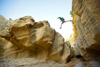 man leaping across rocks while hiking Willis Creek slot cany 20055012275| 写真素材・ストックフォト・画像・イラスト素材|アマナイメージズ
