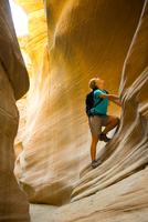 woman hiking through Bull Valley Gorge slot canyon, Panquitc