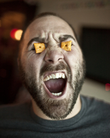 Young bearded man with cheese crackers in his eyes and screa