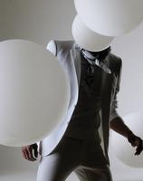 Man with white balloons around him