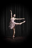 ballerina performing attitude en pointe under spotlight