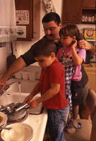 Father washes dishes with his kids