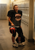 Female football player by school lockers