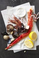 A Setting Of Lemon, Clams, Shrimp, King Crab Leg And Squid
