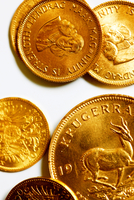 Krugerrand And Other Pure Gold Coins On White Background