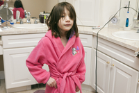 Young Girl Wearing A Pink Robe In A Bathroom