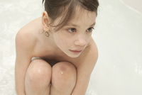 Young Girl Hugging Her Knees In A Bathtub