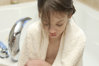 Young Girl In Front Of A Bathtub With Towel Around Her Shoul