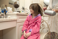 Young Girl Wearing A Pink Robe Getting Her Hair Blown Dry