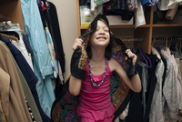Young Girl In An Adult Woman'S Closet Holding A Scarf Over H