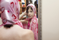 Reflection In A Mirror Of A Young Girl With A Pink Scarf Tie