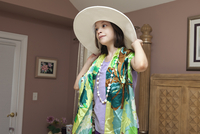 Young Girl Trying On Adult'S Beach Hat, Scarf And Necklace