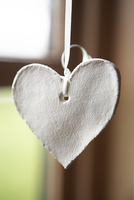 A Ceramic Shaped Heart Hanging In A Window