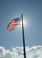 American Flag On Flagpole Backlit By Sun