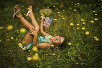 little girl playing in flowers with 2 American Flags during