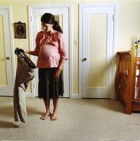 Pregnant Woman In A Pink Top Holding Pants Stretchers And A