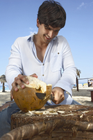 man cutting into a coconut
