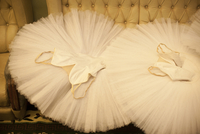 Two white ballet tutus are lying  on a chair.