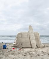 Sand castle art of a van with a surfboard on the beach