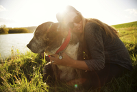 lifestyle image of woman with dog in field