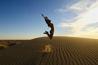 Nude athletic young woman jumping up in the air on a sand dune against a blue sky