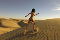 Naked athletic young girl running up a sand dune in a golden sunset glow