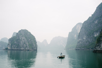 A fisherman rows his craft through Halong Bay, Vietnam