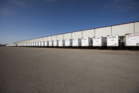 Tractor Trailers parked at loading docks of distribution warehouse.