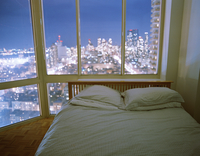 Empty Bed inside of high rise building with view of skyline at night.
