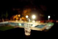 Plastic glass half filled with ice and a straw rest on a table at night with pool lit in the background
