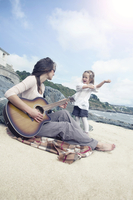 Portrait of young mother playing guitar and her toddler daughter dancing on a sunny beach in Cornwall