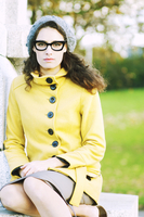 Relaxed portrait of a studious looking young woman in yellow coat and glasses in a park on Autumn day 20055017619| 写真素材・ストックフォト・画像・イラスト素材|アマナイメージズ