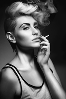 Moody black and white portrait of fashion model with cropped hair and vest top smoking a cigarette