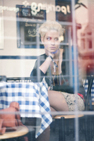 Voyeuristic portrait of young blonde woman thoughtfully looking out of cafe window in Brighton Laines