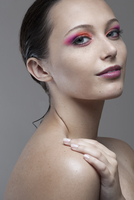 Beauty headshot of smiling young brunette woman with freckles and bright pink eye make-up