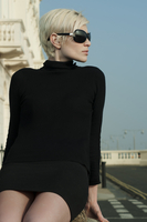 Retro 1960s style portrait of blonde fashion model in black outfit on sunny city street